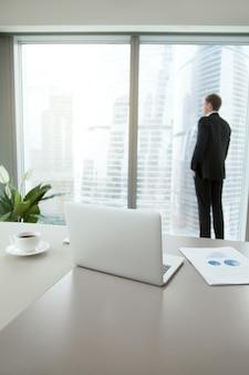 彼のオフィスで考えている自信を持ってビジネス男
