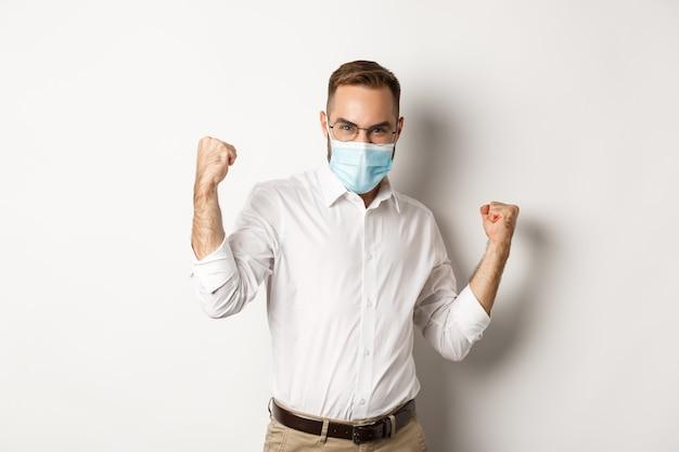 Fiducioso uomo d'affari in maschera medica pompa pugno, gioia di vincere, trionfante in piedi