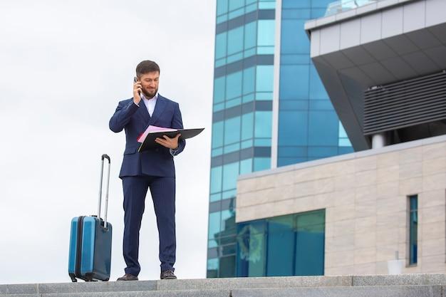 자신감 넘치는 사업가가 사무실 건물 배경 계단에 여행 가방을 들고 서 있다
