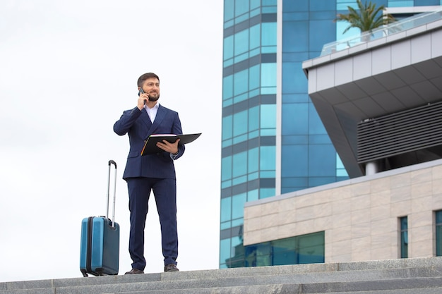 Confident business man stands with a travel suitcase on the steps against office building with a phone and project documents in his hands