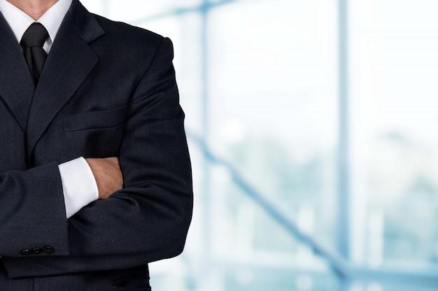 Уверенный деловой человек в элегантном костюме со сложенными руками