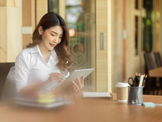Уверенный бизнес-маркетолог читает новости о мировых тенденциях на планшете в офисе. женщина просматривает интернет