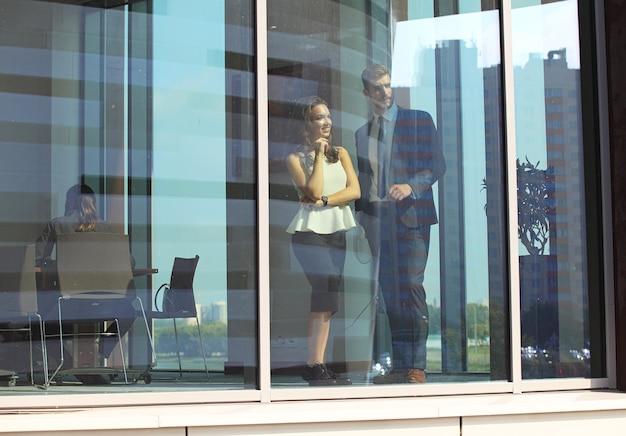 Уверенные деловые партнеры спускаются в офисное здание и разговаривают.