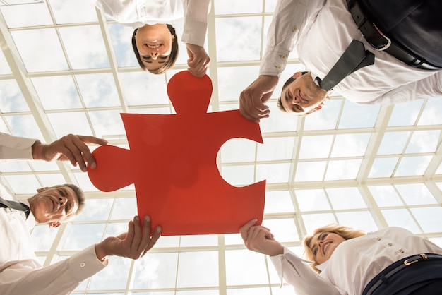 Confident business people holding puzzle together.