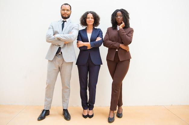 Уверенные деловые люди позируют со сложенными руками