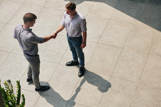 自信を持ってビジネスの人々が握手