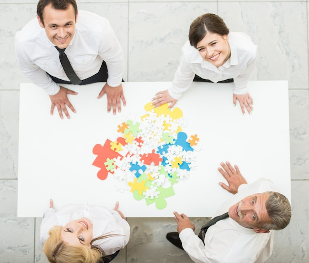 Confident business people wanting to put pieces of puzzle.