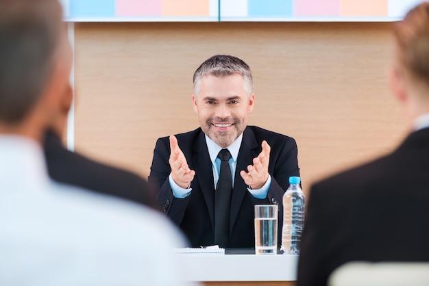 Уверенный бизнес-тренер. веселый зрелый мужчина в формальной одежде делает презентацию в конференц-зале с людьми на переднем плане