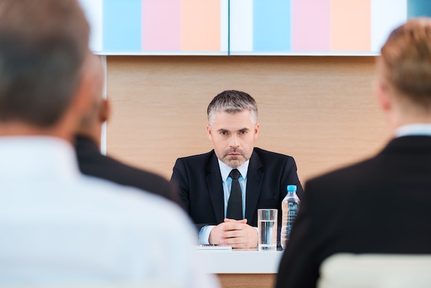 Уверенный бизнес-тренер. уверенный в себе зрелый мужчина в строгой одежде сидит за столом с большим монитором на голове и с людьми на переднем плане
