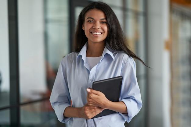 디지털을 들고 젊은 쾌활 한 여성 직원의 직장 초상화에서 자신감 비즈니스 우먼