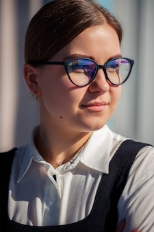 Confident business woman boss standing in modern office wearing glasses, female leader, business owner thinking about future success, planning new opportunities