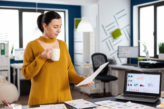 Confident business woman holding documents with statistics enjoying a cup of coffee. executive entrepreneur, manager leader standing working on documents projects, successful corporate professional en