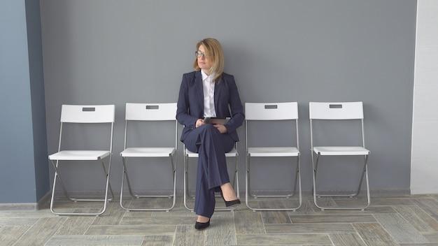 タブレットコンピューターを手で保持している自信を持ってビジネスの女性。オフィスでのビジネスの服の魅力的な女性。ビジネスマンの肖像画。
