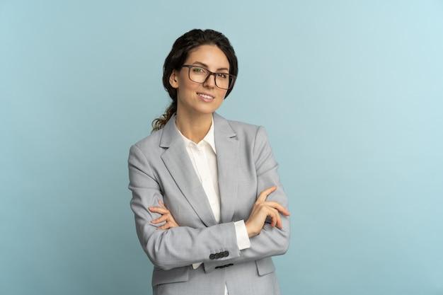 Уверенно деловая женщина, улыбаясь, глядя на камеру, стоя со скрещенными руками, изолированные в студии.