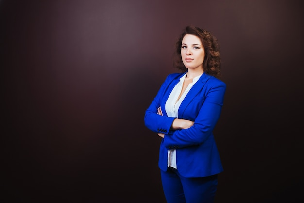 Confident business woman standing in a blue suit with hands clasped.