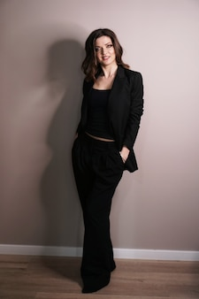 Confident business woman standing full length in black suit on grey