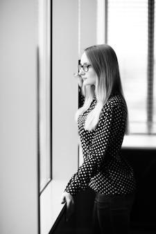 사무실에서 창 근처에 서 있는 자신감 비즈니스 우먼