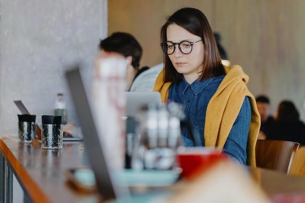 ノートパソコンを持っている自信のあるビジネスウーマンは、コワーキングルームや眼鏡をかけたオフィスの女性で働いています