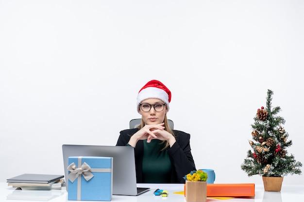 白い背景の上のオフィスでクリスマスツリーとその上に贈り物とテーブルに座っているサンタクロースの帽子を持つ自信のあるビジネス女性