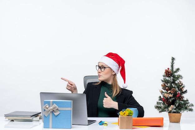 Уверенная деловая женщина в шляпе санта-клауса, сидящая за столом с рождественским деревом и подарком на нем, делая жест и указывая на что-то справа в офисе на белом фоне