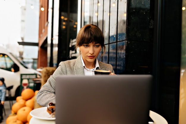 Confident business woman working on laptop on street cafe, typing on keyboard, smart lady seriously looking on screen.