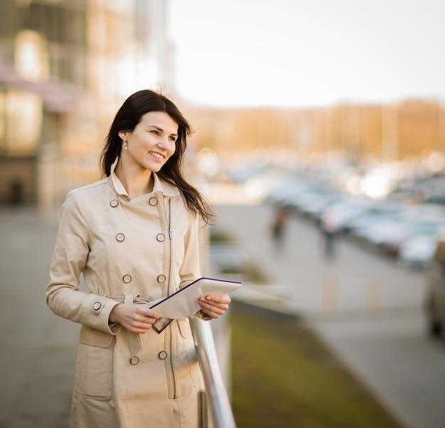 オフィスビルの隣に立って、デジタルタブレットに取り組んでいる自信のあるビジネスウーマン。