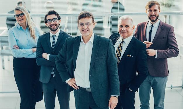 Уверенный бизнесмен и его коллеги, стоя в офисе. концепция совместной работы