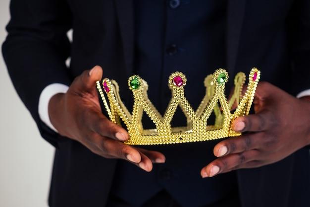 Уверенный бизнесмен бизнес-король в черном классическом костюме с галстуком и очками надевает корону на голову в белом фоне в студии.