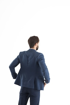 Confident businessman in a business suit standing turned