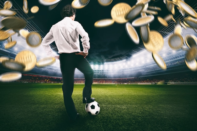 Confident businessman in the center of the soccer field collects a lot of money from the football