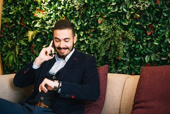 Confident businessman checking time and talking phone