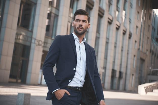 自信を持ってビジネスマン自信を持ってスーツを着た若い男が袖を調整し、目をそらしている間