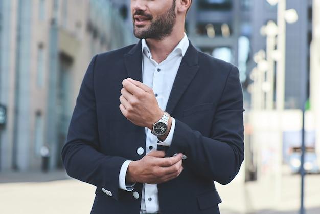 Уверенный бизнесмен обрезал снимок бизнесмена в стильном костюме и поправляет рукав