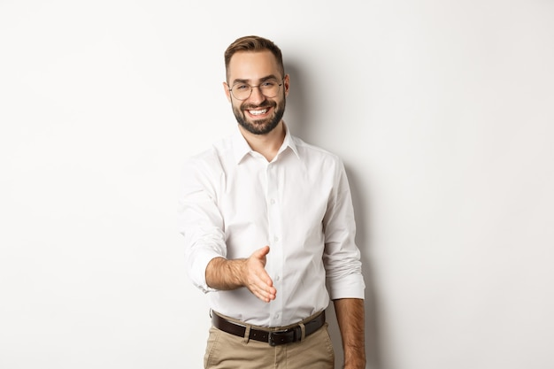 Confident businessman extending hand for handshake, greeting business partner and smiling, standing over white background.