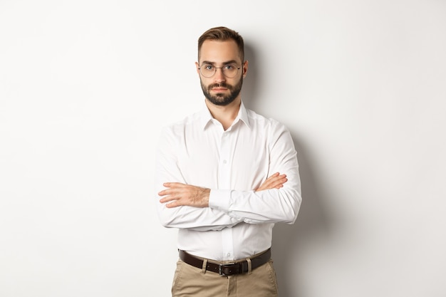 Confident businessman in glasses looking at camera, cross arms on chest, standing over white background.