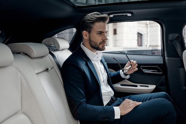 자신감이 사업가. 차에 앉아있는 동안 멀리보고 전체 양복에 잘 생긴 젊은 남자