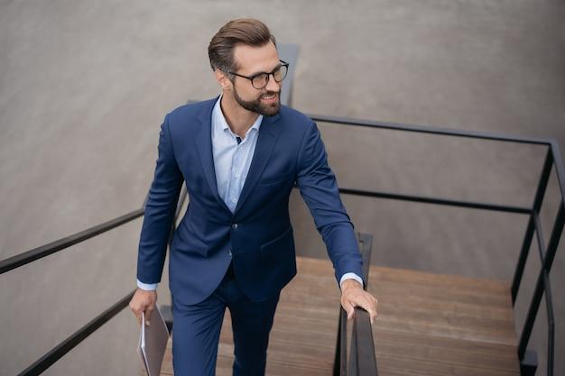 Уверенный бизнесмен, держащий финансовые документы, поднимающийся по лестнице, глядя на пространство для копирования