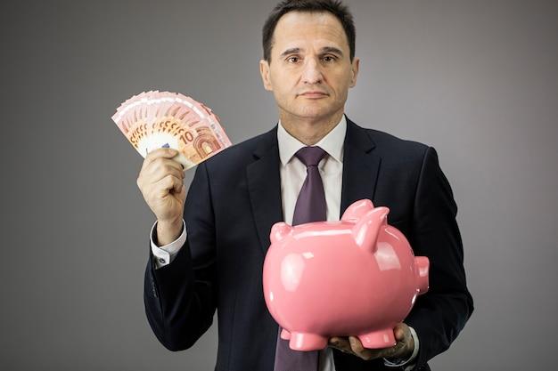 Уверенный бизнесмен держит в руках копилку и деньги банкноты, инвестиции