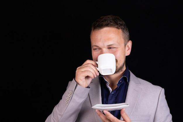 一杯のコーヒーでスーツを着た自信のあるビジネスマンは感情を表現します