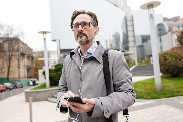 Уверенный бизнесмен в очках с помощью мобильного телефона и наушников во время прогулки по городской улице