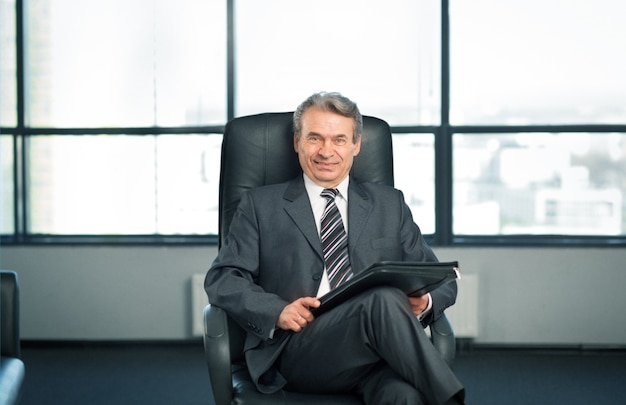 Уверенный бизнесмен в офисе, сидя на стуле в офисе