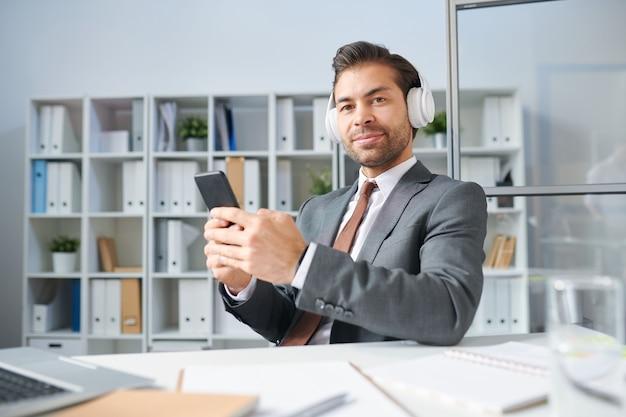 Уверенный бизнесмен в костюме и наушниках, слушающий музыку из плейлиста в своем смартфоне