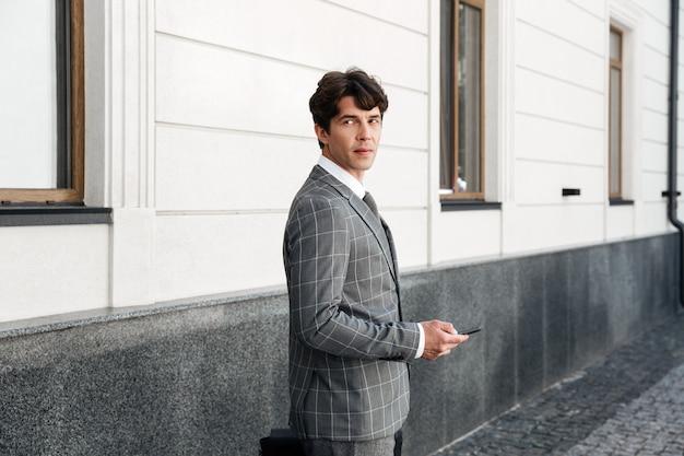 屋外に立っている間車のキーを保持しているスーツで自信を持っているビジネスマン