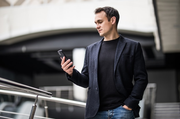 Confident businessman. joyful young man holding mobile phone in office