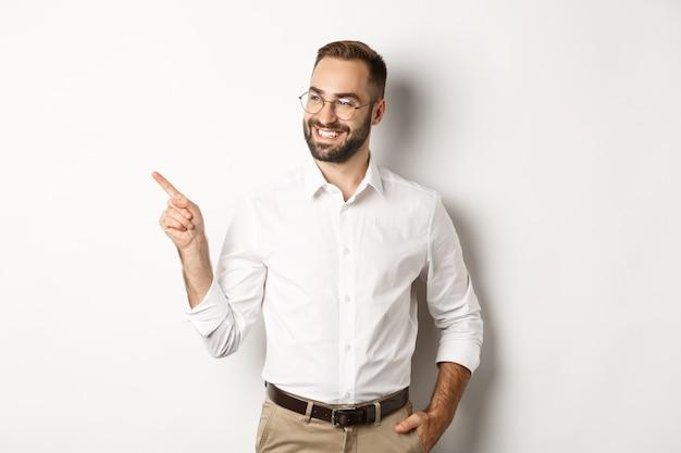 満足しているように見え、指を左に向け、会社のバナーを表示し、白い背景の上に立っている自信のあるビジネスマン。