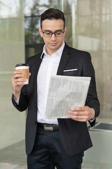 Confident businessman looking through news