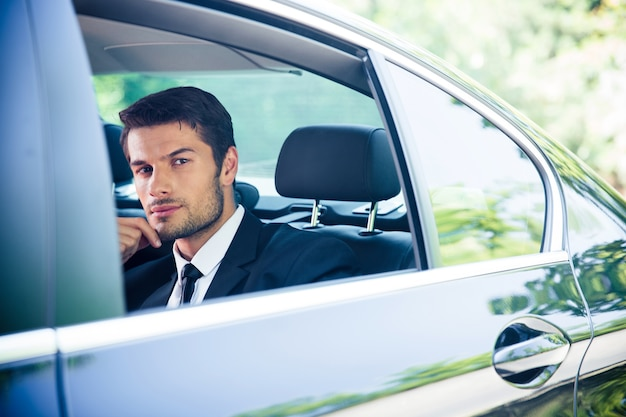 Confident businessman looking at window in car