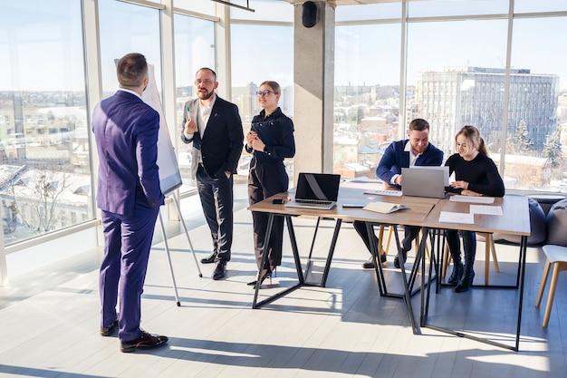 자신감 있는 사업가가 회사 회의에서 회의실에서 새로운 프로젝트를 발표합니다. 아름다운 감사자는 화이트보드와 그래프를 사용하여 비즈니스에 대해 다양한 파트너와 이야기합니다.