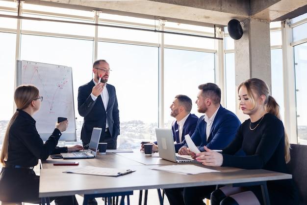 Уверенный бизнесмен делает презентацию нового проекта в зале заседаний на собрании компании. красивые аудиторы разговаривают с разными партнерами о бизнесе, используя доску и графики.