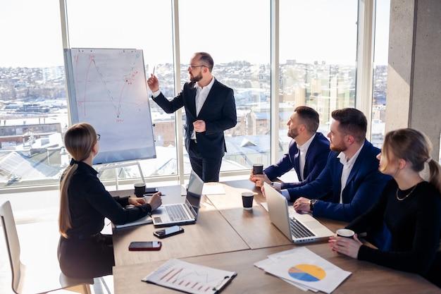 自信のあるビジネスマンは、会社の会議で会議室で新しいプロジェクトのプレゼンテーションを行います。美しい監査人は、ホワイトボードとグラフを使用して、ビジネスについてさまざまなパートナーと話します。